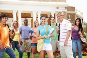 Portrait of happy young students standing outside the university building - Outdoor