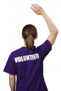 A young woman wearing a volunteer t-shirt stands against a pure white background with back to the camera. Her hand is raised, ready to help.